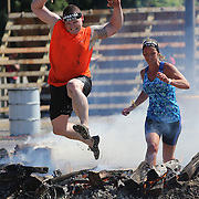 Sean McKenzie in action at the fire jump obstacle during the Reebok Spartan Race. Mohegan Sun, Uncasville, Connecticut, USA. 28th June 2014. Photo Tim Clayton