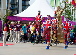 © Licensed to London News Pictures. 28/08/2012, Paralympic Athletes Village, Olympic Park, London. A golden bike carrying the 'The Queen of Ceremonies' arrived into the Olympic village to welcome the Team GB Paralympic athletes ahead of the Paralympic Games official Opening Ceremony.  The performers from the National Youth Theatre put on a performance with dancers dressed in Elizabethan ruffs and urban street-wear.  Photo credit : Alison Baskerville/LNP