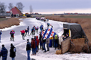 Nederland, Molkwerum, 19970104..De Elfstedentocht in januari 1997 in Friesland..Schaatsers rijden door de polders. Koek en zoopie tent met de Friese vlag. Mensen staan te kijken naar de schaatsers die voorbij komen terwijl de avond valt. Eenzame boerderijen..Schemering. 6000 schaatsers en meer dan een miljoen toeschouwers..The Elfstedentocht is a speed skating competition and leisure skating tour in the province of Friesland in the Netherlands..Skaters driving towards the setting sun.6.000 skaters and over a million spectators were present. The route takes the skaters through eleven cities in Frisia, in the North of Holland. Flag of the provence Friesland. 200 kilometre race along the frozen canals of Friesland..Skaters ride through the polders. Cake and zoopie tent with the Frisian flag. People are watching the skaters that come as evening falls. Isolated farms.