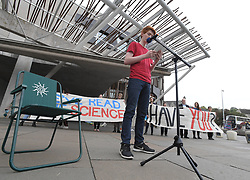 Pictured: Sandy Boyd, from Youth Climate Strikers Scotland reads from the report.<br /> <br /> Climate activists held a vigil and read the UN IPCC report outside the Scottish Parliament today.<br /> <br /> © Dave Johnston / EEm
