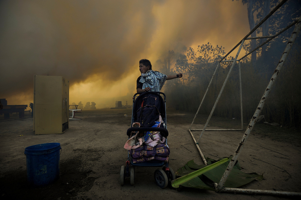 Un joven grita por ayuda al ver su casa completamente cubierta por humo en el poblado de Zámbiza. Durante una sequía de dos meses, aproximadamente 2565 incendios forestales, (muchos presuntamente provocados) quemaron 3796 hectareas de bosques, algunas casas y muchos animales silvestres en las laderas boscosas que rodean Quito, la capital del Ecaudor.   Ningún humano murió, pero tomaran décadas antes de que las áreas afectadas se recuperen.