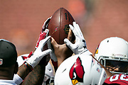 The Arizona Cardinals join hands as they hold a football in the air during the 2018 NFL regular season week 2 football game against the Los Angeles Rams on Sunday, Sept. 16, 2018 in Los Angeles. The Rams won the game in a 34-0 shutout. (©Paul Anthony Spinelli)