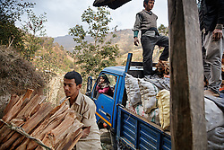 With the help of other villagers, Durga loads wood and potatoes into the truck while his eldest daughter Sumitra, 10, sits inside. He would drive overnight to Kathmandu, where they would be sold wholesale to a market vendor.<br />