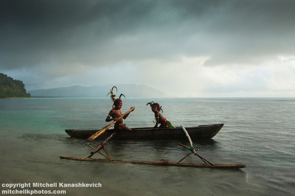 Two traditional tribal boys  in a canoe in the bay at the village of Labo, South West Bay, Malekula, Vanuatu