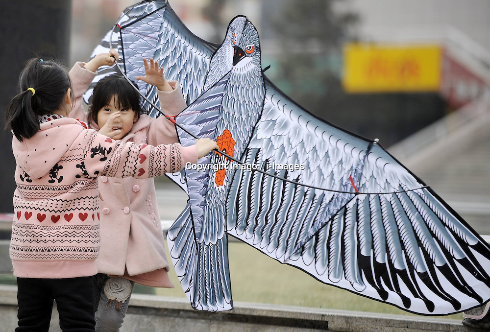 Two girls fly a kite on Guangming Square in Yinchuan, capital of northwest China s Ningxia Hui Autonomous Region, March 16, 2013. As temperatures rises, many parents start to take their children to do some outdoor activities. , March 16, 2013. Photo by Imago / i-Images...UK ONLY.Contact..
