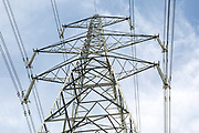 Looking up from below at pylon and high voltage electricity power lines against blue sky, UK
