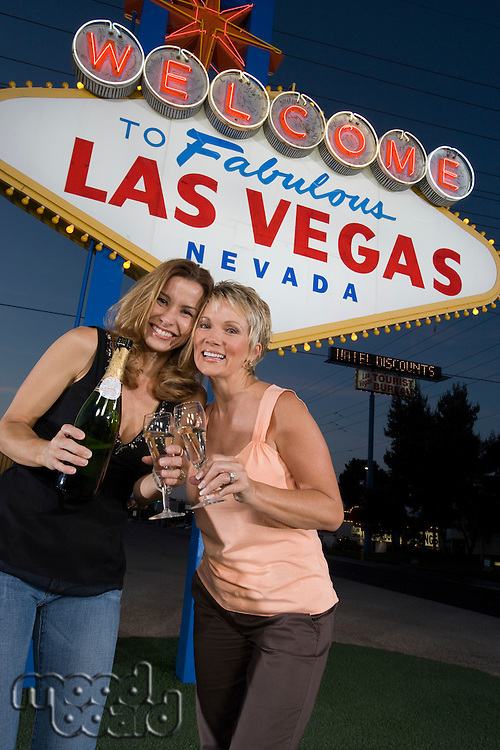 Two women toasting in front of Welcome to Las Vegas sign, portrait
