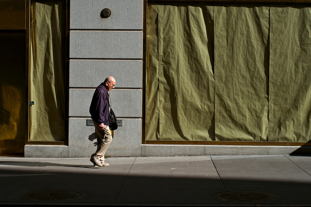 Man walking past papered-over shop windows, Wall Street