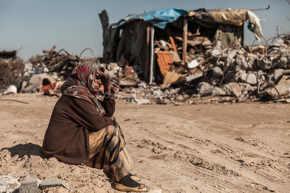 Kufha quartiere a sud della striscia di Gaza. Un'altra zone molto colpita   dall'attacco israeliano &quot;Margine protettivo&quot;. Il quartiere &egrave; stato raso al suolo. La popolazione, a distanza di sei mesi dalla fine della guerra, vive tra le macerie della propria casa, al freddo, senza luce, gas e acqua. Molti dormono in container o in case improvvisate o dentro le macerie della loro casa.<br />  Nella foto una donna seduta sul ciglio di una strada dove ci sono solo macerie e case distrutte.