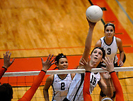 1 Nov. 2011 -- EDWARDSVILLE, Ill. -- Belleville West High School girls' volleyball player Emily Becker (19) leaps to spike the ball past blockers from Edwardsville High School during the IHSA Class 4A girls volleyball sectional semifinal at Edwardsville High School in Edwardsville, Ill. Tuesday, Nov. 1, 2011. Edwardsville won, 2-1. Photo © copyright 2011 Sid Hastings.