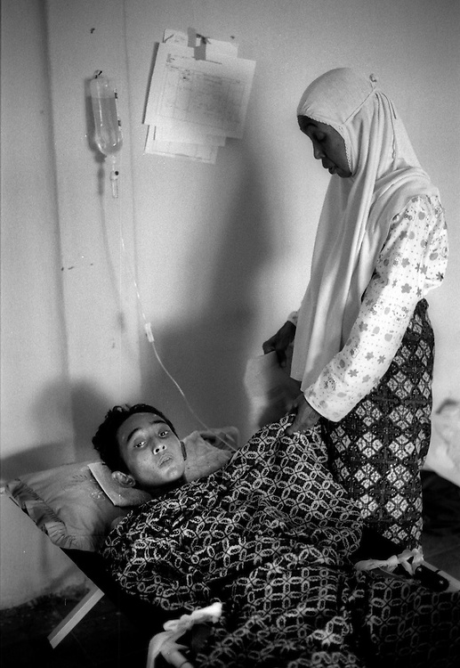 Comforted by his grandmother, Lut Nuraini, 17 year old Teuku Sofyan was alleged to have survived 8 days in the wreck of a boat washed up in Banda Aceh by the Tsunami that struck on December 26, 2004, killing many thousands of people. Kesdam Hospital, Banda Aceh January 2005