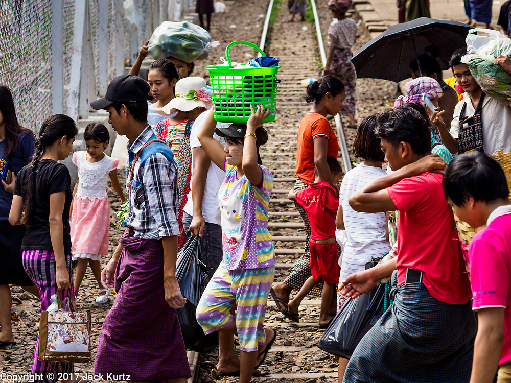 25 NOVEMBER 2017 - YANGON, MYANMAR: Passengers who got off the Yangon Circular Train walk across the tracks in Danyingon station, in the middle of the train's loop. The Yangon Circular Train is a 45.9-kilometre (28.5 mi) 39-station two track loop system connects satellite towns and suburban areas to downtown. The train was built during the British colonial period, the second track was built in 1954. Trains currently run both directions (clockwise and counter-clockwise) around the city. The trains are the least expensive way to get across Yangon and they are very popular with Yangon's working class. About 100,000 people ride the train every day. A a ticket costs 200 Kyat (about .17¢ US) for the entire 28.5 mile loop.    PHOTO BY JACK KURTZ