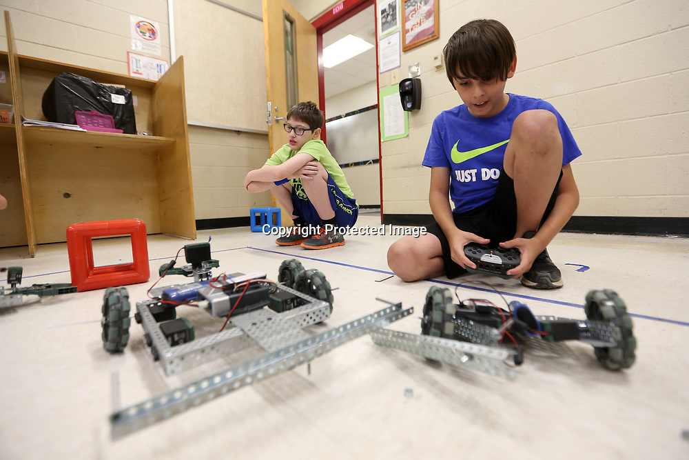 """Thomas Smith, 12, drives the robot he and Drew Long built in the VEX Robotics class at the Tupelo Public School District's Camp Opportunity held at Lawndale Elementary School. Smith built the robot with his teammate Drew Long, 12, and called it """"The Fidgety of Death"""", built for speed and destruction so they can take out other robots in the battle games they play against other teams."""