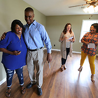 Kimberly Jeter, left, gets a congratualtory hug from Sean Suggs before her home dedication Friday morning.