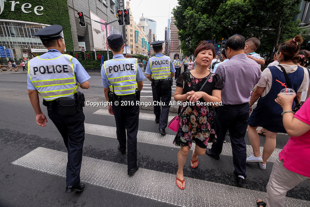 "Police officers patrol along the Nanjing Road Pedestrian Street on September 5, 2016, in Shanghai, China. Nanjing Road is the main shopping street of Shanghai, China, and is one of the world's busiest shopping streets. The street is named after the city of Nanjing, capital of Jiangsu province neighbouring Shanghai. Today's Nanjing Road comprises two sections, Nanjing Road East and Nanjing Road West. In some contexts, ""Nanjing Road"" refers only to what was pre-1945 Nanjing Road, today's Nanjing Road East, which is largely pedestrianised. Before the adoption of the pinyin romanisation in the 1950s, its name was rendered as Nanking Road in English. Shanghai is the most populous city in China and the most populous city proper in the world. It is one of the four direct-controlled municipalities of China, with a population of more than 24 million as of 2014. It is a global financial centre, and a transport hub with the world's busiest container port. Located in the Yangtze River Delta in East China, Shanghai sits on the south edge of the mouth of the Yangtze in the middle portion of the Chinese coast. The municipality borders the provinces of Jiangsu and Zhejiang to the north, south and west, and is bounded to the east by the East China Sea. A major administrative, shipping, and trading town, Shanghai grew in importance in the 19th century due to trade and recognition of its favourable port location and economic potential. The city was one of five forced open to foreign trade following the British victory over China in the First Opium War while the subsequent 1842 Treaty of Nanking and 1844 Treaty of Whampoa allowed the establishment of the Shanghai International Settlement and the French Concession. The city then flourished as a center of commerce between China and other parts of the world (predominantly Western countries), and became the primary financial hub of the Asia-Pacific region in the 1930s. However, with the Communist Party takeover of the mainland in 1949, tra"