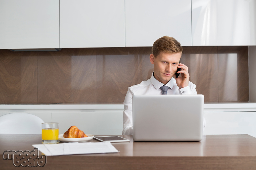 Mid adult businessman on call while using laptop at breakfast table