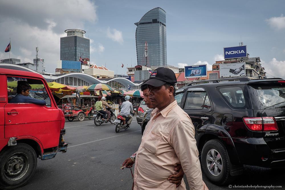 Wie hier vor dem Central Market herrscht Im Stadtzentrum Pnomh Penh stets emsiges Treiben. Im Hintergrund richten sich die zwei einzigen Hochhäuser der Stadt auf, links der ältere Phnom Penh Tower sowie rechts der eben erst fertiggestellte, 188 Meter hohe Vattanac Capital Tower.