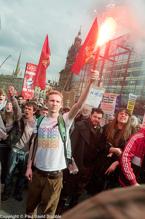 Student Demonstrator holds a light flare in  Barkers Pool, outside Sheffield city Hall where the Liberal Democrats are holding their Party conference Conference Sheffield Saturday.12 March 2011.Images © Paul David Drabble