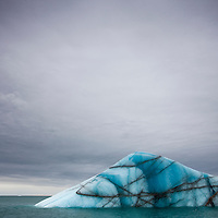 Norway, Svalbard, Nordaustlandet, Deep blue iceberg floating near face of Brasvellbreen Icefield on stormy summer morning