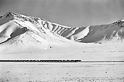 IRAN, ARAK:  Train crossing a snowy plateau in the mountains of Iran.  Black and white dramatic landscape print.