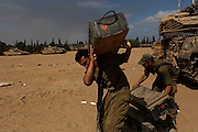 Israeli soldiers carry cases at a staging area near the border with the Gaza Strip.
