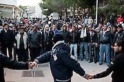 LAMPEDUSA. UN CORDONE DI SICUREZZA COMPOSTO DA IMMIGRATI TUNISINI CONTENGONO LA FOLLA DI IMMIGRATI ALL'INTERNO DEL CENTRO DI PERMANENZA TEMPORANEO DURANTE LE FASI DI TRASFERIMENTO DEGLI STESSI IMMIGRATI PRESSO I CENTRI DI PERMANENZA TEMPORANEI DI SICILIA E CALABRIA;