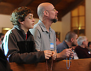 A father and son pray the rosary before Mass during a men's conference in Appleton. (Sam Lucero photo)