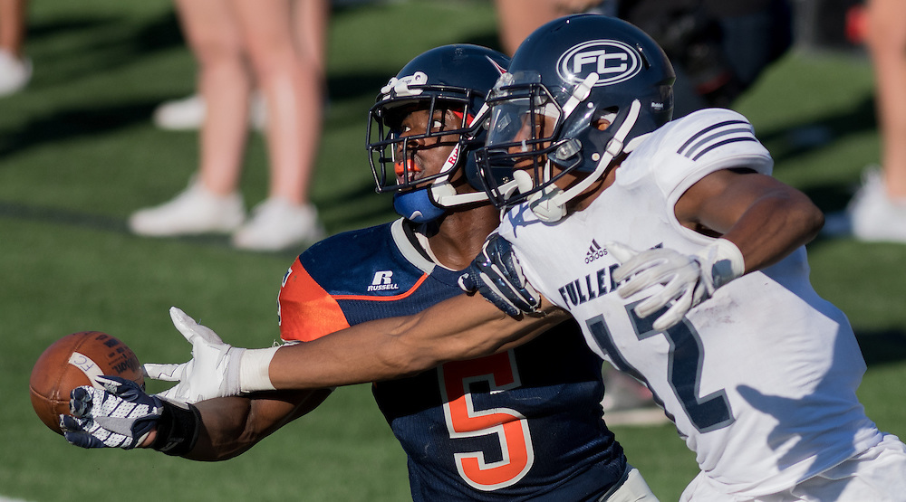 (date)(time) -- Fullerton College wide receiver Justin Walker (12) reaches for a pass defended by Orange Coast College defensive back Semaj Bilial (5) during the second half of a CCCAA football game in Costa Mesa, CA.-- Photo by Colter Peterson / Sports Shooter Academy