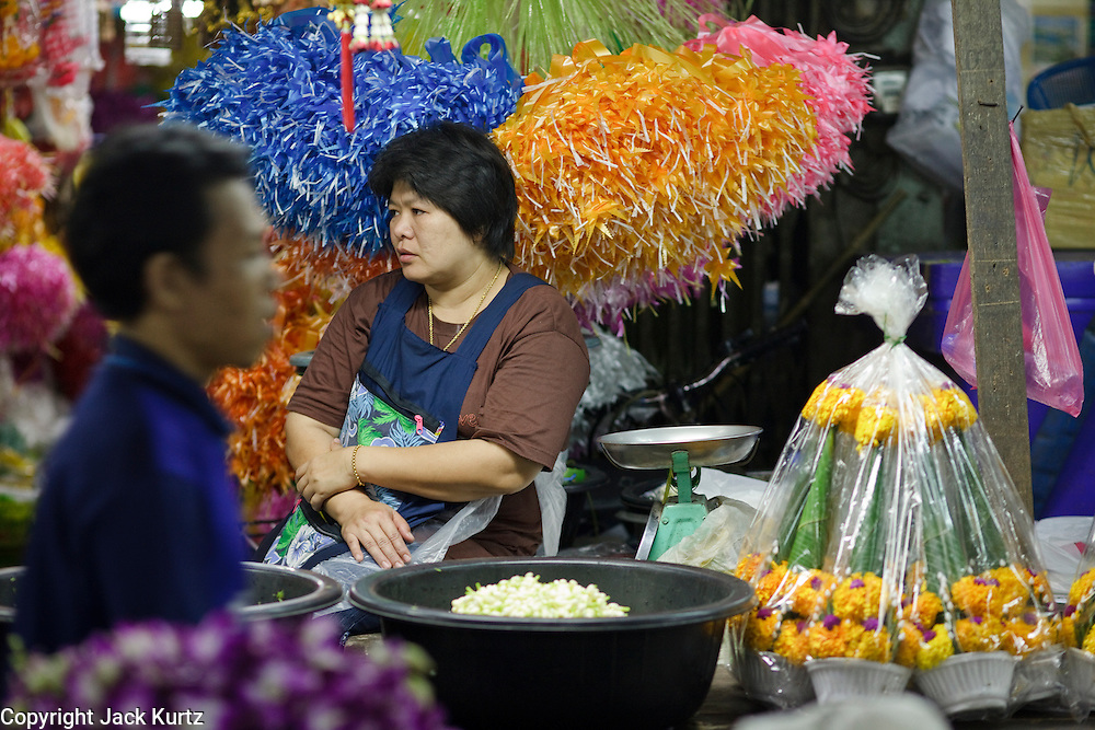 "Mar. 9, 2009 -- BANGKOK, THAILAND: A garland vendor waits for customers in the flower and produce market on the Chao Phraya River in Bangkok. Every morning, flowers and produce from the provinces arrive in the market where they are bundled and sold at retail in Bangkok's consumer markets. Many of the flowers are sold in and around the Buddhist temples in Bangkok. People buy them as offerings or to ""make merit."" Photo by Jack Kurtz / ZUMA Press"