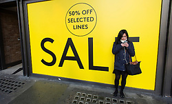 © Licensed to London News Pictures. 20/12/2014. London, UK. Christmas shoppers on London's Oxford Street on the last saturday before Christmas walk past a Warehouse storefront displaying sales discounts. Photo credit : Richard Isaac/LNP
