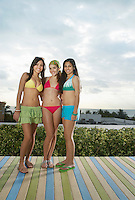 Three teenage girls (16-17) wearing bikinis standing on wooden deck portrait
