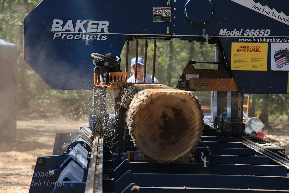 Heavy duty bandsaw mills bark off trees at ultra-mechanized clearcutting of an Ozarks woodland at Missouri In Woods Logging Demo near Viburnum, Missouri.