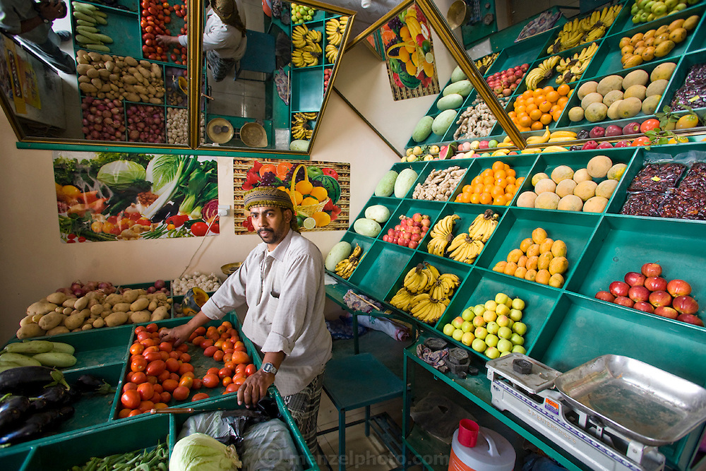 A vendor at his vegetable and fruit market stall at Al-Hawta souk, Hadhramawt, Yemen.