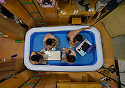 WUHAN, CHINA - AUGUST 05: (CHINA OUT) <br /> <br /> Student Brings An Inflatable Pool Into His Dorm To Avoid Wuhan's Hot Weather<br /> <br /> Students play a game of cards as they cool off in an inflatable pool at Huazhong Normal University on August 5, 2014 in Wuhan, Hubei Province of China. Students who stayed on their college campus over summer have resorted to various ways to defeat the persistent hot weather in Wuhan. A student in Huazhong Normal University purchased a small inflatable pool to put in his dorm. The pool can hold a few students at a time, providing a space for them to cool off while they play cards, go on the Internet or even take a nap. <br /> ©Exclusivepix