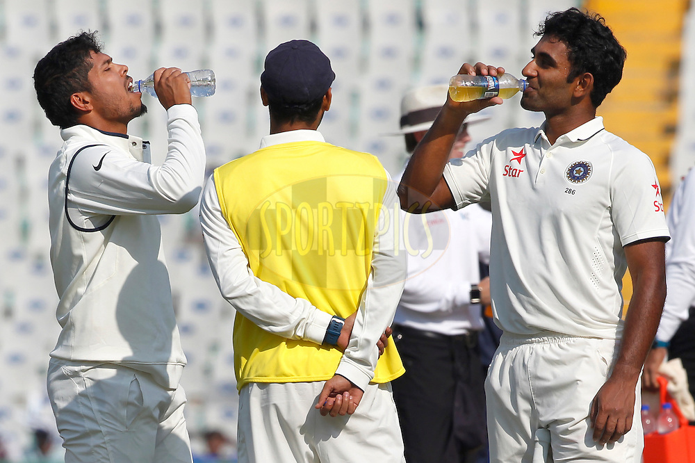 Jayant Yadav of India and Umesh Yadav of India drinking during day 3 of the third test match between India and England held at the Punjab Cricket Association IS Bindra Stadium, Mohali on the 28th November 2016.<br /> <br /> Photo by: Deepak Malik/ BCCI/ SPORTZPICS