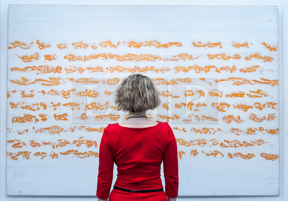 "© Licensed to London News Pictures. 19/05/2016. London, UK. A visitor looks at Judit Reigl's ""Progress"".  Art16 opens at Olympia, in west London.  Now in its fourth edition, the fair brings together over 100 galleries from more than 30 countries showcasing a diverse cross-section of work by contemporary artists from around the world for buyers and art enthusiasts to visit. Photo credit : Stephen Chung/LNP"