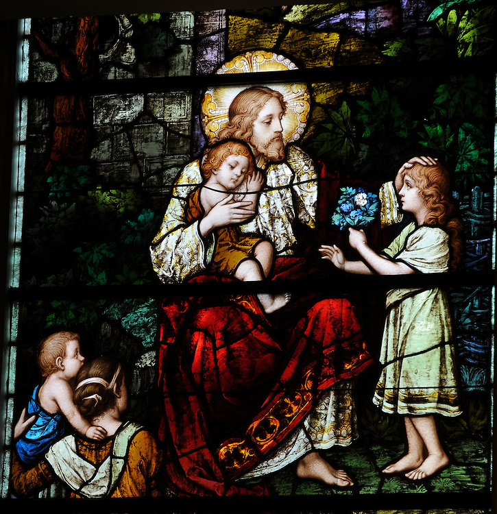 Stained glass image of Jesus with children. (photo by Sam Lucero)