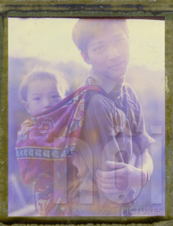 Polaroid 79's portrait of young father carrying his son on his back.