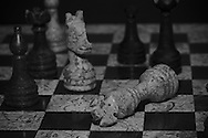 A King lays fallen on the field of battle while a pawn retreats