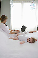 Mother sits typing on laptop with baby beside her on bed