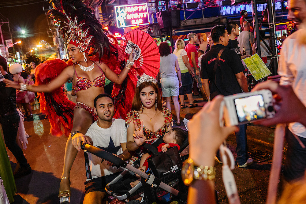 Tourists stop to take pictures with lady boys on Bangla Street.