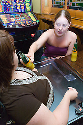 Non disabled woman passing a drink to her disabled friend whilst out at the pub,  The condition means it's necessary for the woman to drink through a straw,