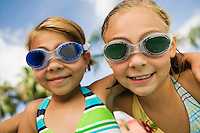 Two girls (7-9) wearing swim goggles portrait.