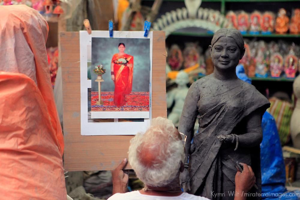 Asia, India, Calcutta. Clay artist sculpts from photograph in the potter's village of Kumartuli in Calcutta.