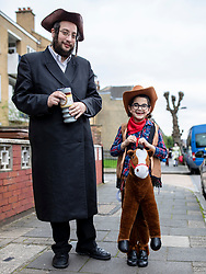 © Licensed to London News Pictures. 21/03/2019. London, UK. An Orthodox Jewish man and his son, in fancy dress, celebrate the festival of Purim on the streets of Stamford Hill in north London on 21 March 2019. Purim celebrates the miraculous salvation of the Jews from a genocidal plot in ancient Persia, documented in the Book of Esther. Traditionally the jewish community wear fancy dress and exchange gifts of food and drink. Photo credit: Rob Pinney/LNP