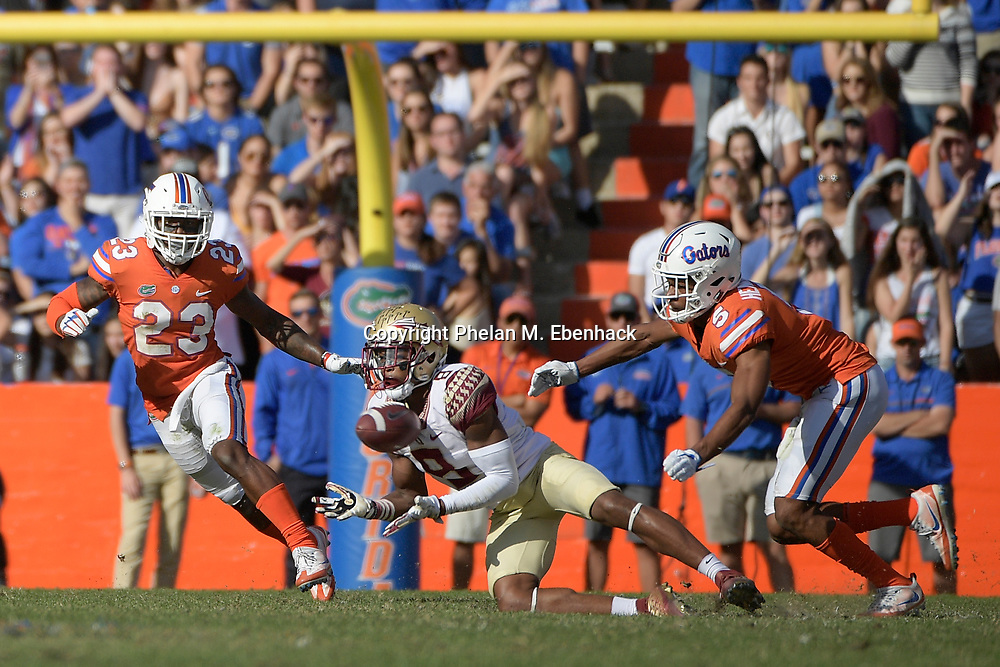 Florida State wide receiver Nyqwan Murray (8) attempts to catch a pass between Florida defensive back Chauncey Gardner Jr. (23) and cornerback CJ Henderson (5) during the second half of an NCAA college football game Saturday, Nov. 25, 2017, in Gainesville, Fla. FSU won 38-22. (Photo by Phelan M. Ebenhack)