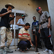 A group of rebel fighters prepare their weapons for an attack on pro-Gaddafi troops positions in central Zawiyah.