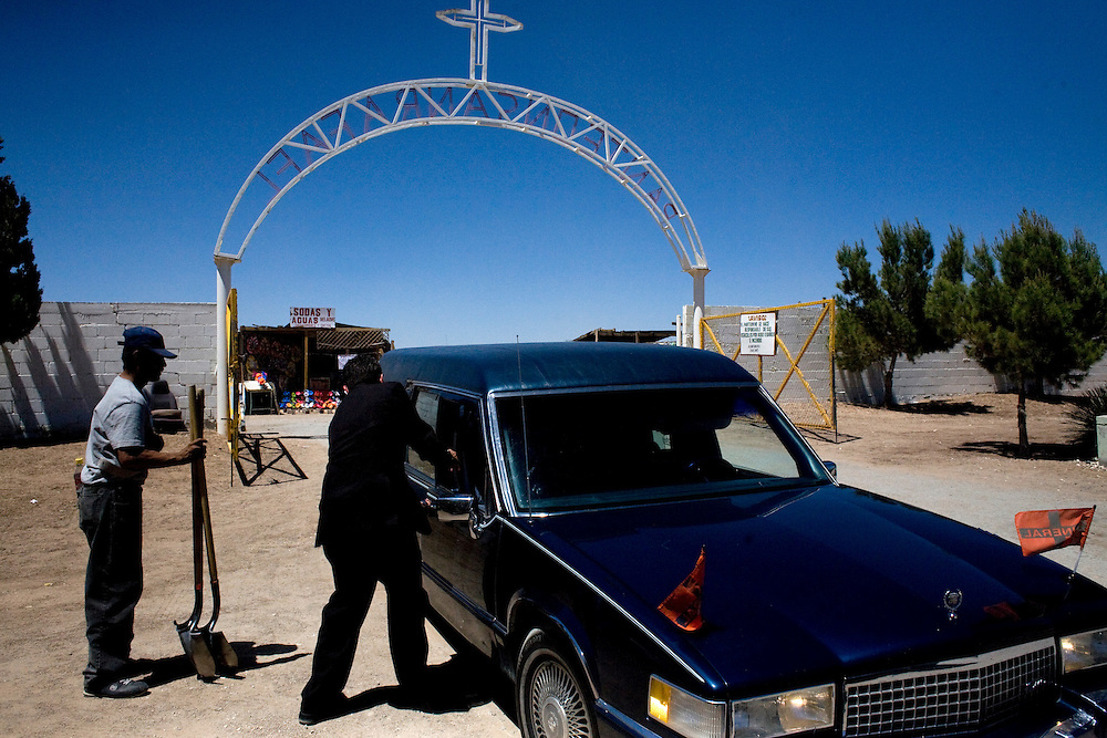 A hearse picks up a grave digger on the way to a funeral in Ciudad Juarez, Chihuahua on May 21, 2010.