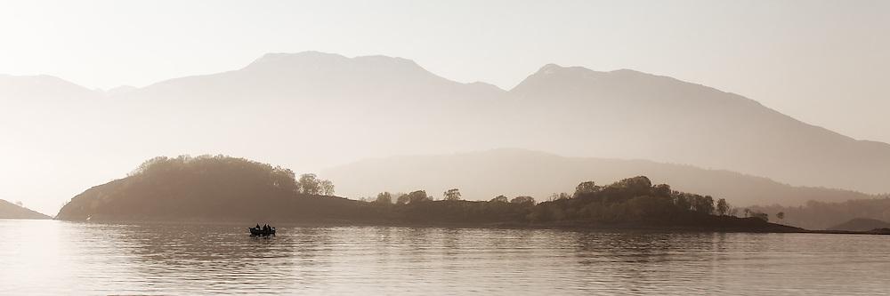 A boat with people fishing in the early morning | En båt med personer som fisker tidlig en morgen