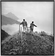 Berglandwirtschaft: ein Paar trägt eine Milchkanne; agriculture de montagne, travail en commun: un couple transporte une boille à lait